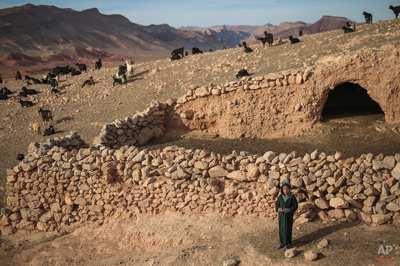 In this Thursday, Feb. 4, 2016 photo, Fatima, 5, poses for a picture outside a cave where she lives with her family, in the desert of the Anti-Atlas mountains, east of Ourazazate, Morocco. Today the Amazigh rely on cattle and agriculture as their main sources of income and maintain a nomadic lifestyle closely resembling that of their ancestors. Some live in clay houses with no electricity or running water while a few still dwell with their sheep and goats in remote mountain caves. Others live closer to the towns at the Atlas foothills, benefiting from modern amenities. (AP Photo/Mosa'ab Elshamy)