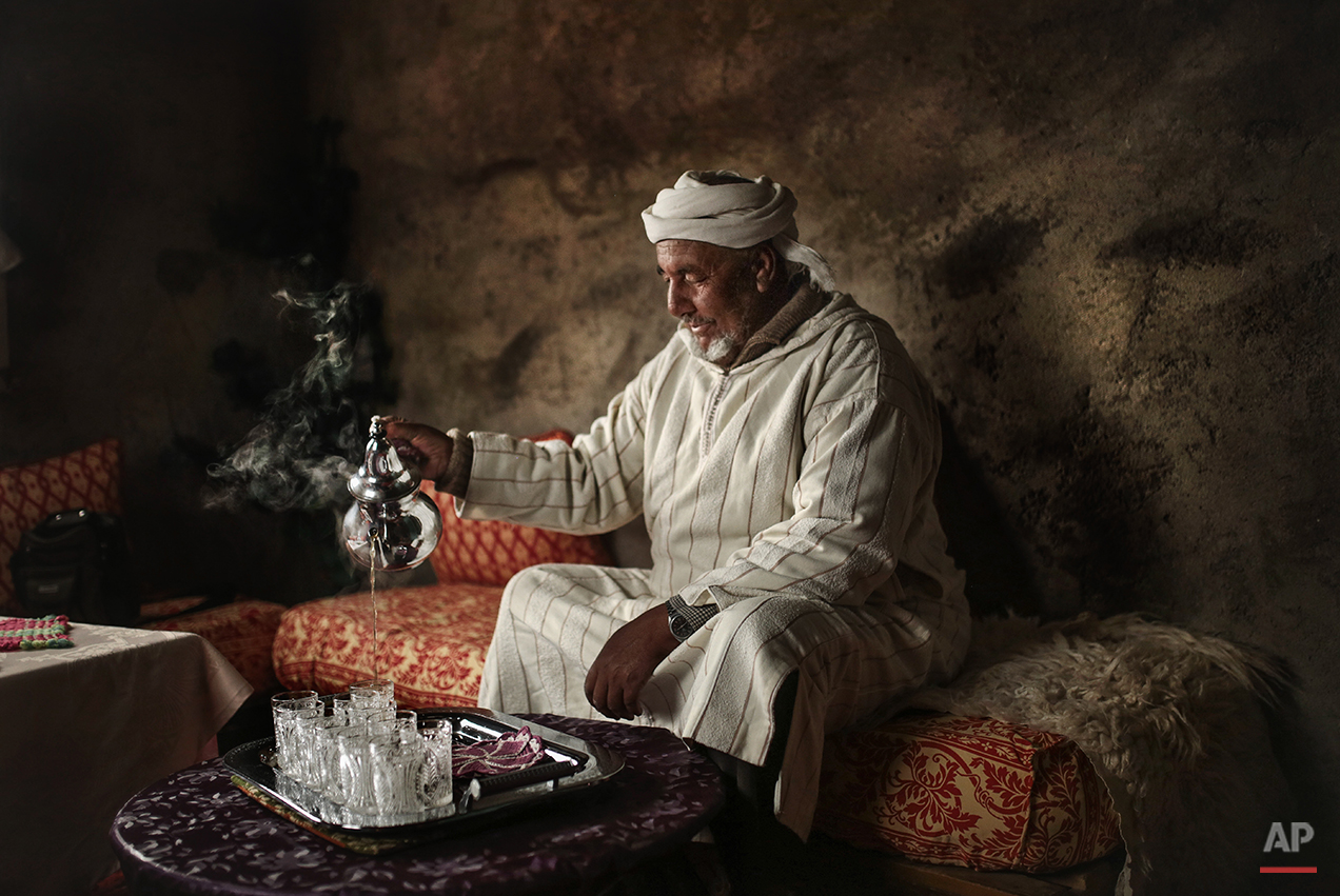 In this Friday, Feb. 5, 2016 photo, Hajj Saeed, 56, an Amazigh villager, pours tea for guests at his home in the Middle Atlas town of Tounfit, near the province of Midelt, central Morocco. Across North Africa, the Berbers number about 50 million. At least 15 million Moroccans are Amazigh, divided into different groups according to their dialects. While they speak the native Amazigh language of Tamazight, which has a large number of dialects and recently gained recognition as an official language in Morocco, many have adopted Arabic as part of a long process of Arabization and Islamization. (AP Photo/Mosa'ab Elshamy)