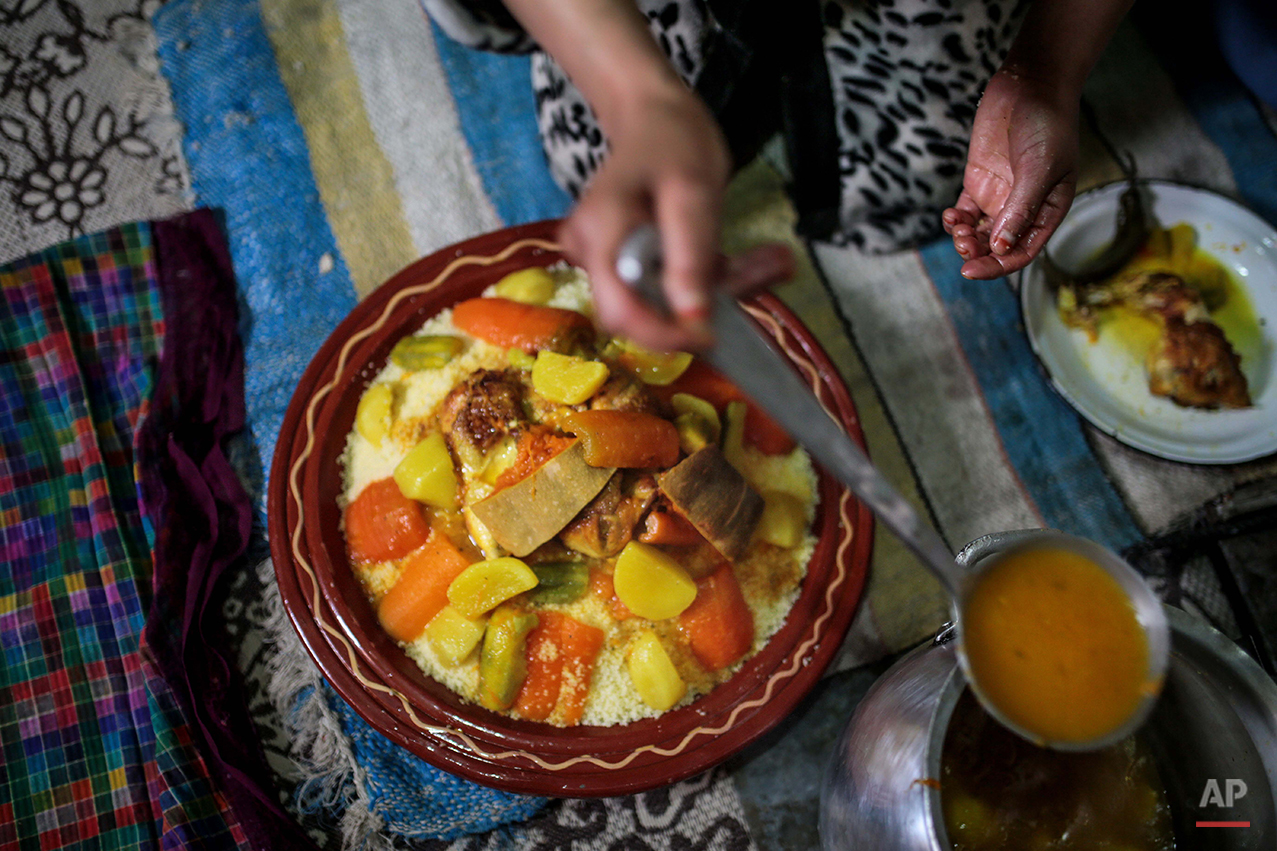 In this Friday, Feb. 5, 2016 photo, Fatima, 36, prepares a meal of Couscous, a traditionally Amazigh dish, at her home in a town near Tounfit in the Middle Atlas, central Morocco. Today the Amazigh rely on cattle and agriculture as their main sources of income and maintain a nomadic lifestyle closely resembling that of their ancestors. Some live in clay houses with no electricity or running water while a few still dwell with their sheep and goats in remote mountain caves. Others live closer to the towns at the Atlas foothills, benefiting from modern amenities. (AP Photo/Mosa'ab Elshamy)