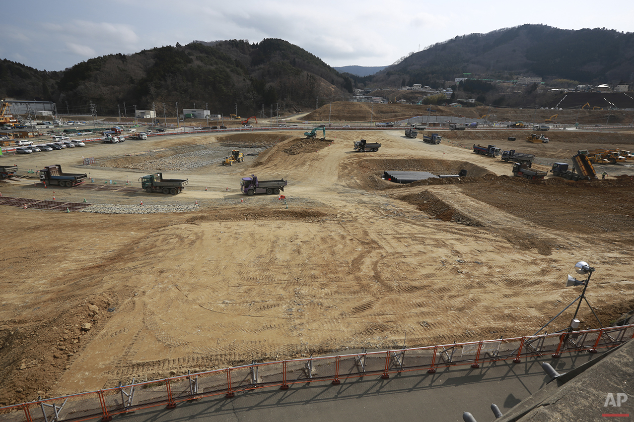 In this Saturday, March 5, 2015 photo, trucks wait in queue to dump soils in the tsunami and earthquake destroyed town of Onagawa, Miyagi Prefecture, northern Japan. Five years after the disaster, construction work is clearly underway but far from done. Rebuilt roads stretch to the horizon between still largely vacant expanses. It is a massive undertaking to raise the ground level of entire neighborhoods, to better protect them from inundation, before rebuilding from scratch. (AP Photo/Eugene Hoshiko)