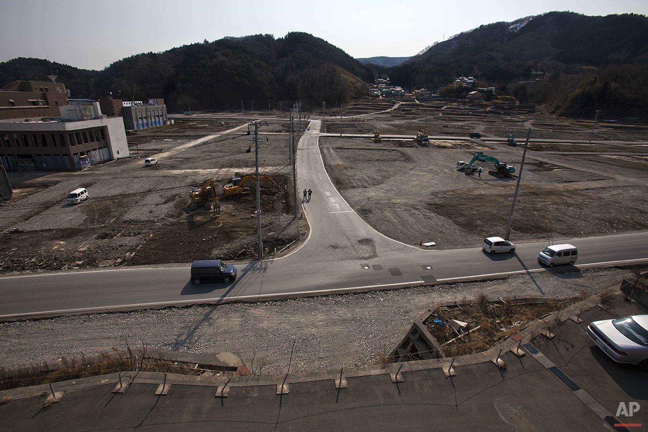 In this Feb. 22, 2012 photo, two officials walk along a street in the tsunami and earthquake destroyed town of Onagawa, Miyagi Prefecture, northern Japan. (AP Photo/David Guttenfelder)