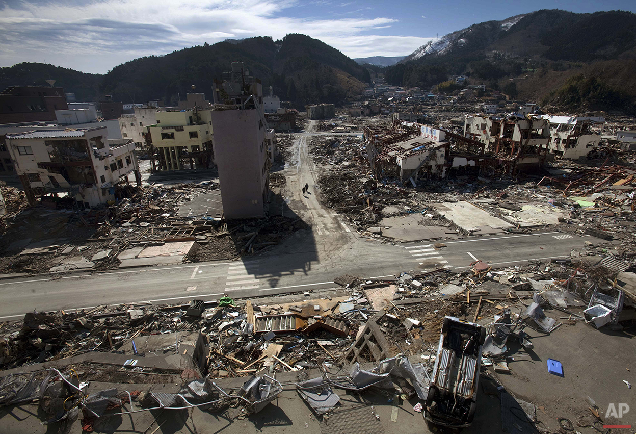 In this March 19, 2011 photo, residents of the tsunami- and earthquake-destroyed town of  Onagawa, Miyagi Prefecture in northeastern Japan walk down an empty street. (AP Photo/David Guttenfelder)