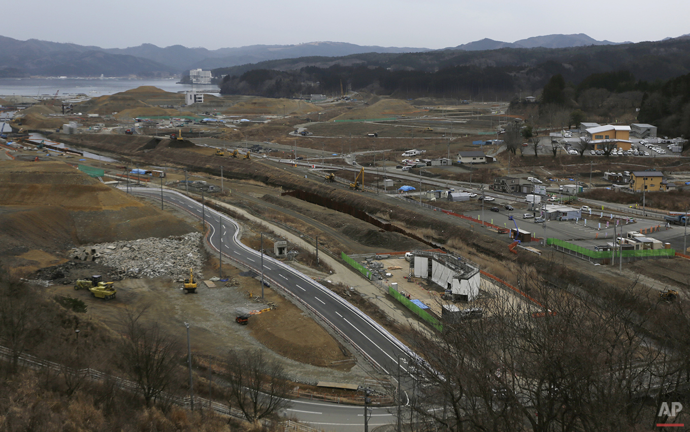 In this Monday, March 7, 2016 photo, construction works go on in the leveled city of Minamisanriku, Miyagi Prefecture, northeastern Japan, almost five years after the March 11, 2011 tsunami. (AP Photo/Eugene Hoshiko)