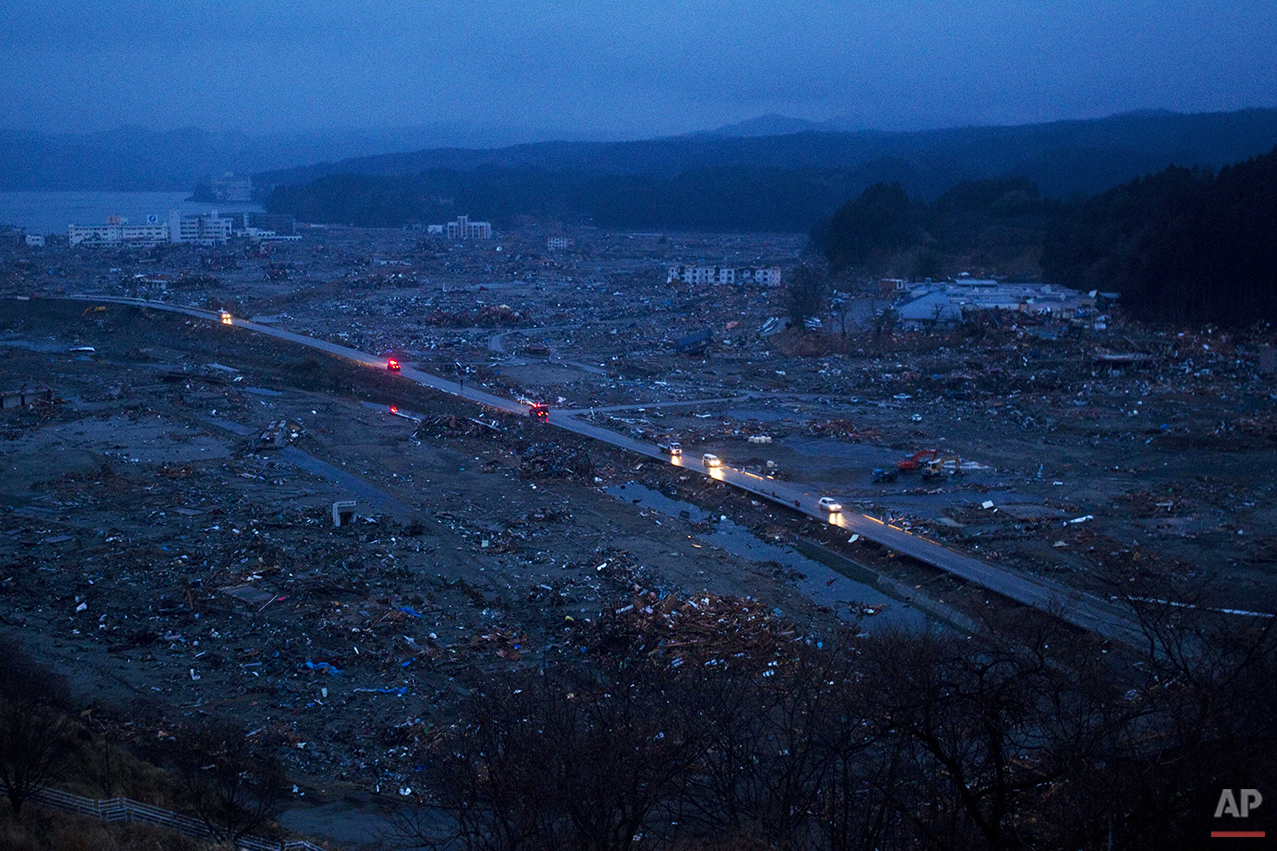 In this March 15, 2011 photo, vehicles pass through the ruins of the leveled city of Minamisanriku, Miyagi Prefecture, northeastern Japan. (AP Photo/David Guttenfelder)