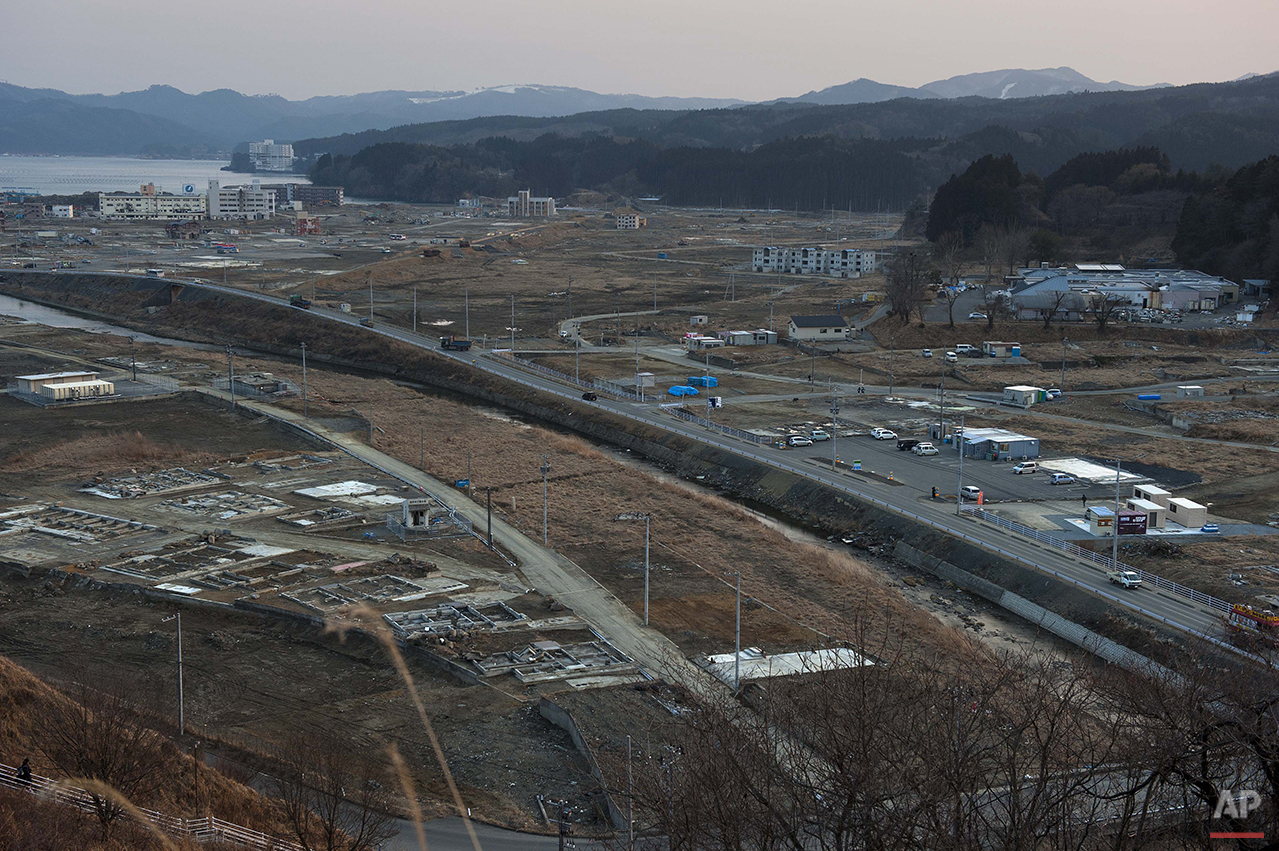 In this Feb. 23, 2012 photo, vehicles pass through the ruins of the leveled city of Minamisanriku, Miyagi Prefecture, northern Japan, almost one year after the March 11, 2011 tsunami. (AP Photo/David Guttenfelder)