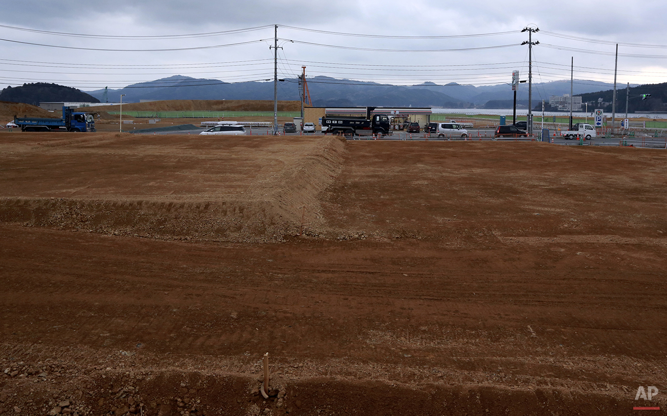 In this Saturday, March 5, 2016 photo, trucks and cars drive through the leveled city of Minamisanriku, Miyagi Prefecture, northern Japan. Five years after the disaster, construction work is clearly underway but far from done. Rebuilt roads stretch to the horizon between still largely vacant expanses. It is a massive undertaking to raise the ground level of entire neighborhoods, to better protect them from inundation, before rebuilding from scratch. (AP Photo/Eugene Hoshiko)