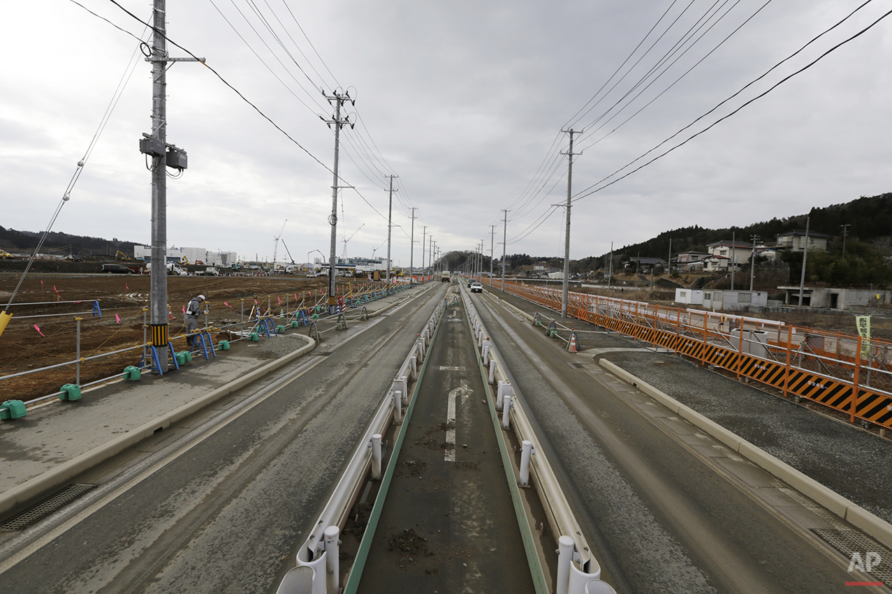 In this Monday, March 7, 2016 photo, a worker checks the construction site in Kesennuma, Miyagi Prefecture, northeastern Japan. Five years after the disaster, construction work is clearly underway but far from done. Rebuilt roads stretch to the horizon between still largely vacant expanses. It is a massive undertaking to raise the ground level of entire neighborhoods, to better protect them from inundation, before rebuilding from scratch. (AP Photo/Eugene Hoshiko)