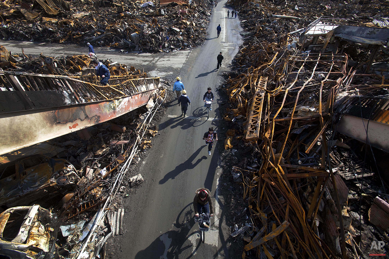 In this March 17, 2011 photo, Japanese residents of Kesennuma, Miyagi Prefecture, northeastern Japan, are seen from a destroyed pedestrian bridge, passing through a road that was cleared by a bulldozer through the ruins of the city, six days after the March 11 tsunami. (AP Photo/David Guttenfelder)