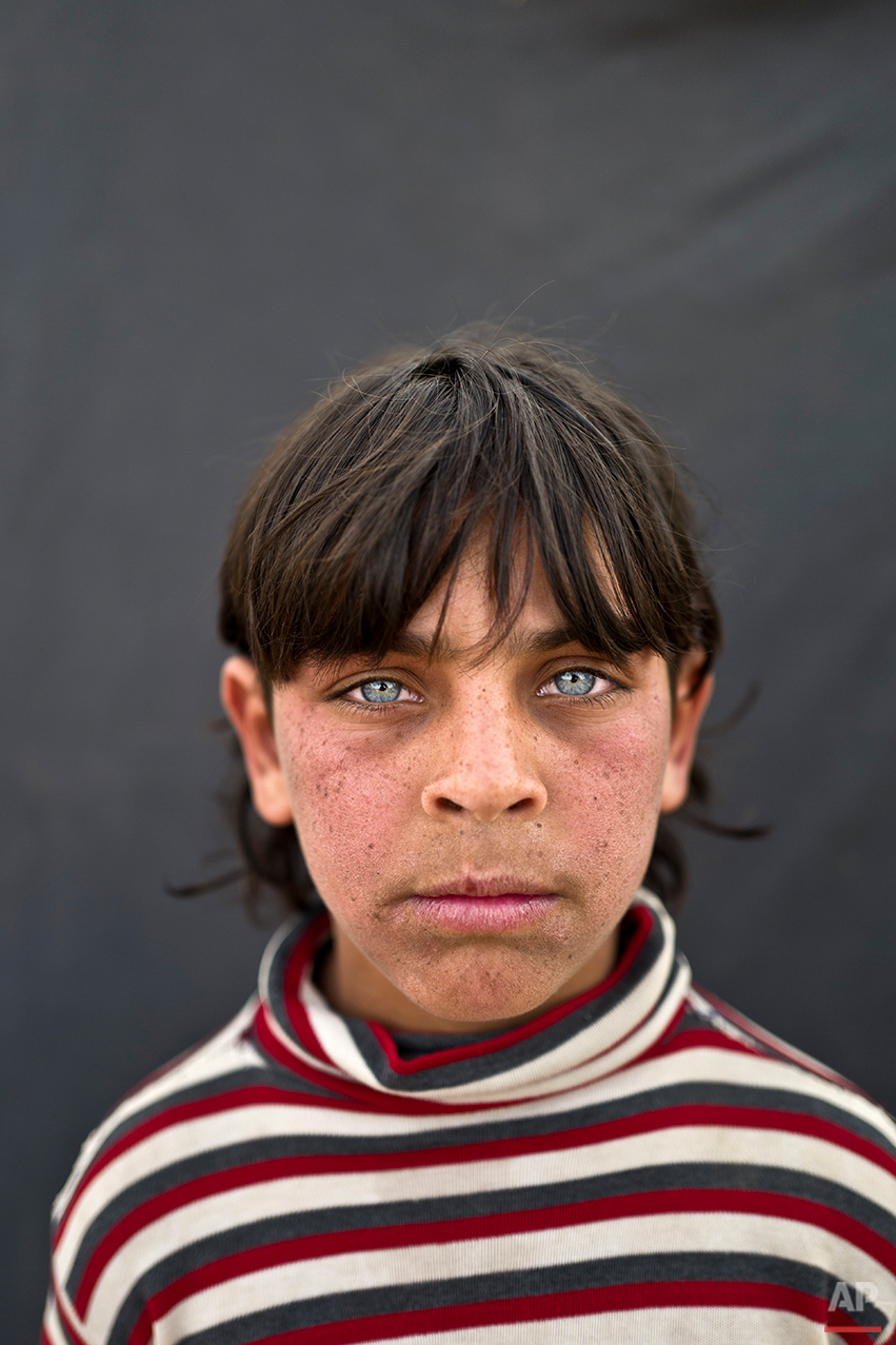 """In this Saturday, March 12, 2016 photo, Syrian refugee boy Rakan Raslan, 11, from Hama, Syria, poses for a picture at an informal tented settlement near the Syrian border on the outskirts of Mafraq, Jordan. """"I used to go to the school back in Hama,"""" Raslan said. """"I used to have friends there. Our home was destroyed in the war and we had to flee to Jordan."""" Rakan said that without an education, his future is in doubt. """"The best I can become is a driver,"""" he said. (AP Photo/Muhammed Muheisen)"""