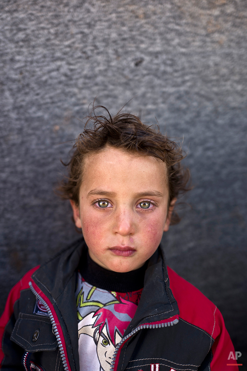 In this Monday, March 14, 2016 photo, Syrian refugee boy Hammad Khadir, 3, from Hassakeh, Syria, poses for a picture at an informal tented settlement near the Syrian border on the outskirts of Mafraq, Jordan. The U.N. agency for children said in a report this week that close to 3 million Syrian children are not in school as a result of the conflict, including some 700,000 refugee children. (AP Photo/Muhammed Muheisen)