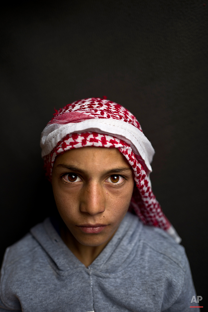 """In this Sunday, March 13, 2016 photo, Syrian refugee boy Mohammed Bandar, 12, from Hama, Syria, poses for a picture at an informal tented settlement near the Syrian border on the outskirts of Mafraq, Jordan. """"I want to become a doctor to be able to help people,"""" says Bandar. (AP Photo/Muhammed Muheisen)"""