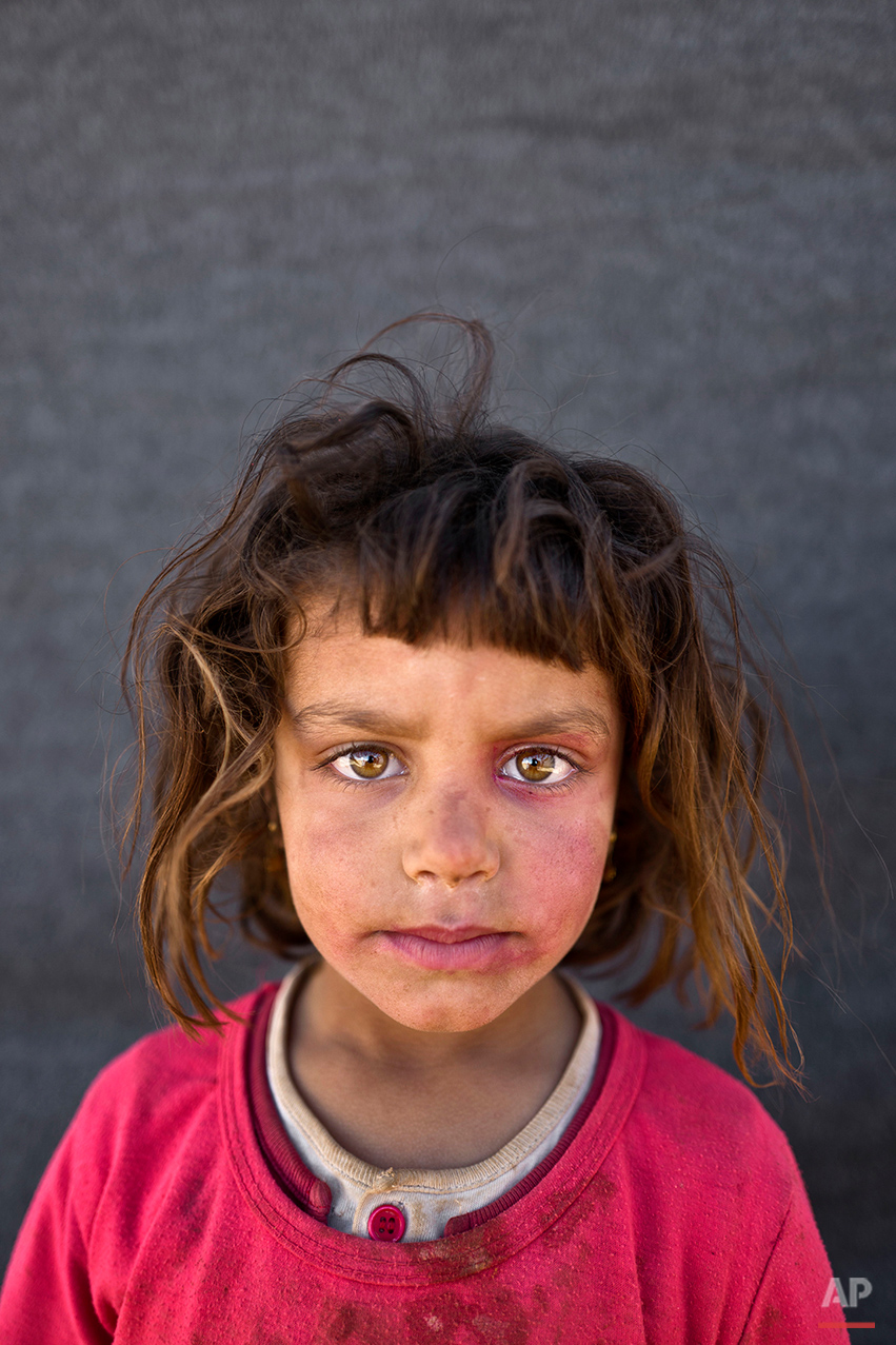 "In this Friday, March 11, 2016 photo, Syrian refugee girl Mona Emad, 5, from Hassakeh, Syria, poses for a picture at an informal tented settlement near the Syrian border on the outskirts of Mafraq, Jordan. ""I want to go back to Syria but my father told us that he wants to go to The United States of America,"" says Mona. (AP Photo/Muhammed Muheisen)"