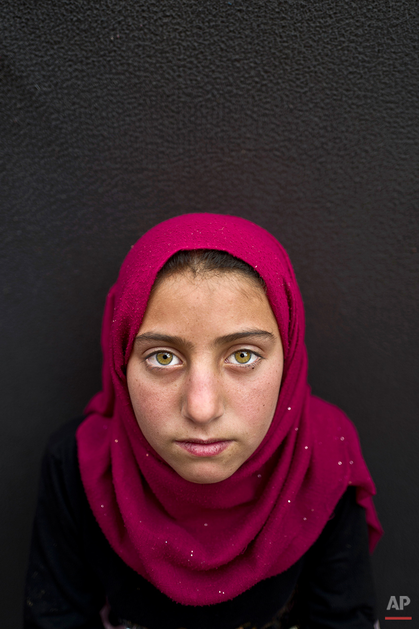 "In this Sunday, March 13, 2016 photo, Syrian refugee girl Yasmeen Mohammed, 11, from Eastern Ghouta, Syria, poses for a picture at an informal tented settlement near the Syrian border on the outskirts of Mafraq, Jordan.  Mohammed, whose family fled their town, said she misses her old life. ""All I want is to go back to my school in Syria and see my friends,"" she said. (AP Photo/Muhammed Muheisen)"