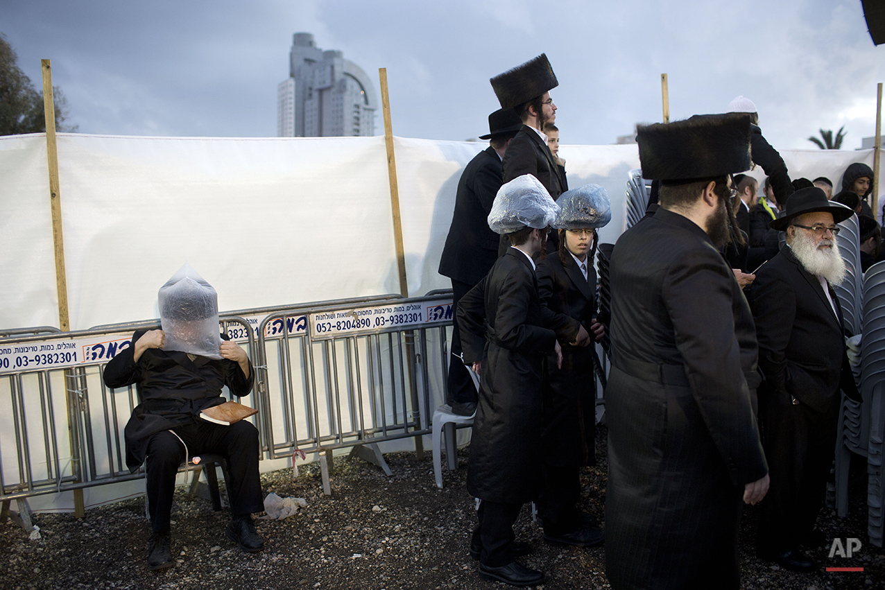 An Ultra-Orthodox Jewish man covers his hat with a plastic bag to avoid rain during the wedding of the grandson of the Rabbi of the Tzanz Hasidic dynasty community, in Netanya, Israel, Tuesday, March 15, 2016. (AP Photo/Oded Balilty)