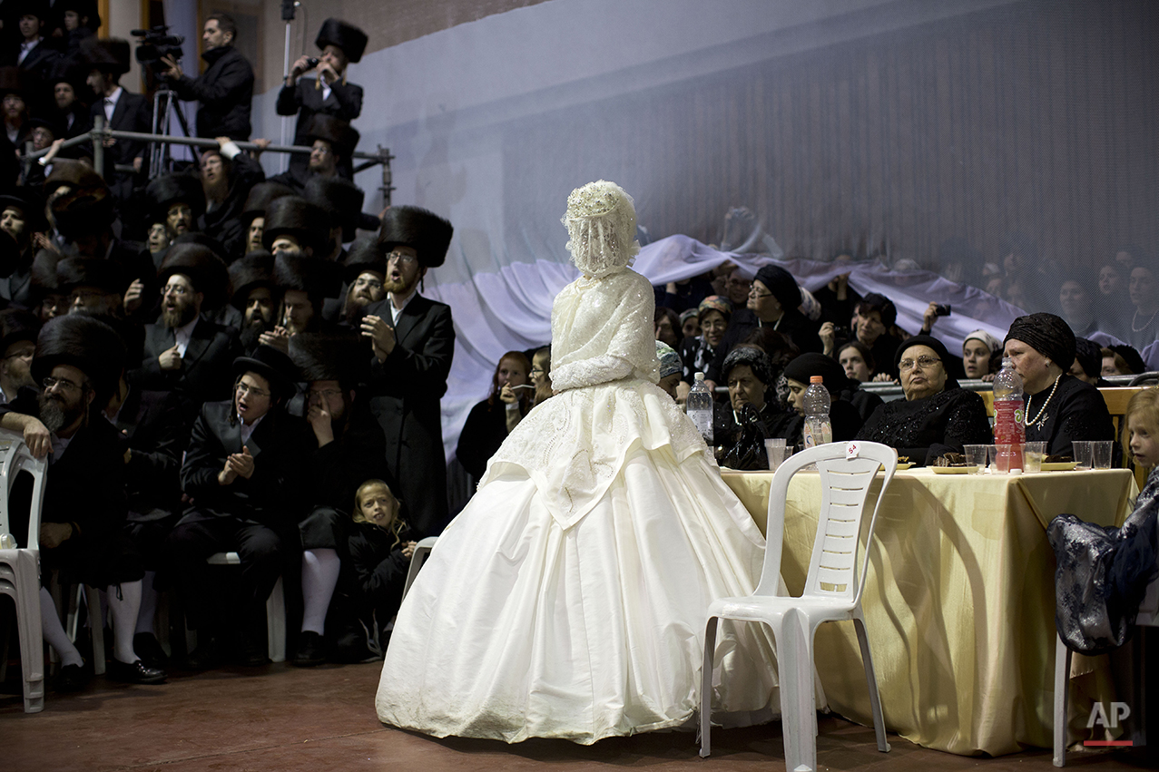 An ultra-Orthodox Jewish bride enters to the men's section of the wedding, to fulfill the Mitzvah tantz, in which family members and honored rabbis are invited to dance in front of the bride, often holding a gartel, and then dancing with the groom, during her wedding to the grandson of the Rabbi of the Tzanz Hasidic dynasty community, in Netanya, Israel, Wednesday, March 16, 2016. (AP Photo/Oded Balilty)