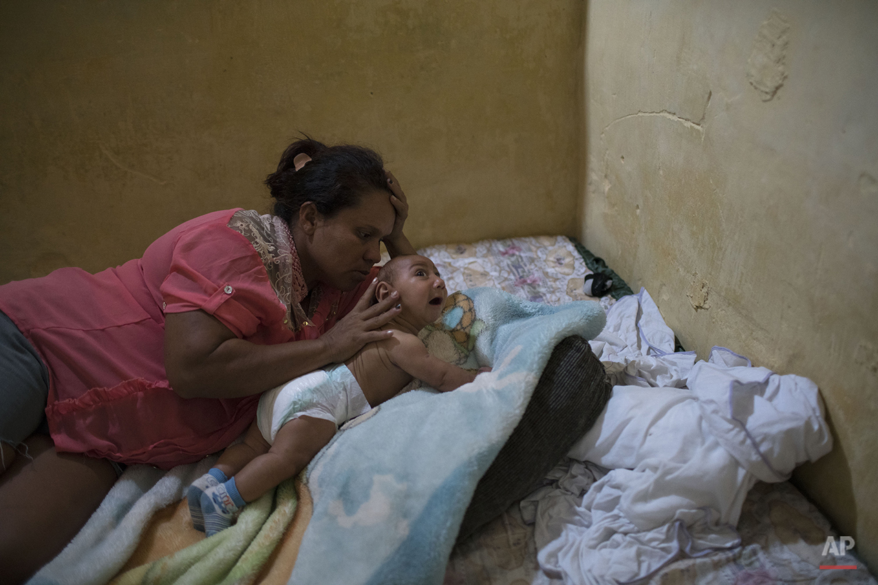 """In this Jan. 30, 2016 photo, Solange Ferreira tries to make her son Jose Wesley sleep, in Bonito, Pernambuco state, Brazil. We were lucky to learn about the bucket,"""" said Ferreira. (AP Photo/Felipe Dana)"""