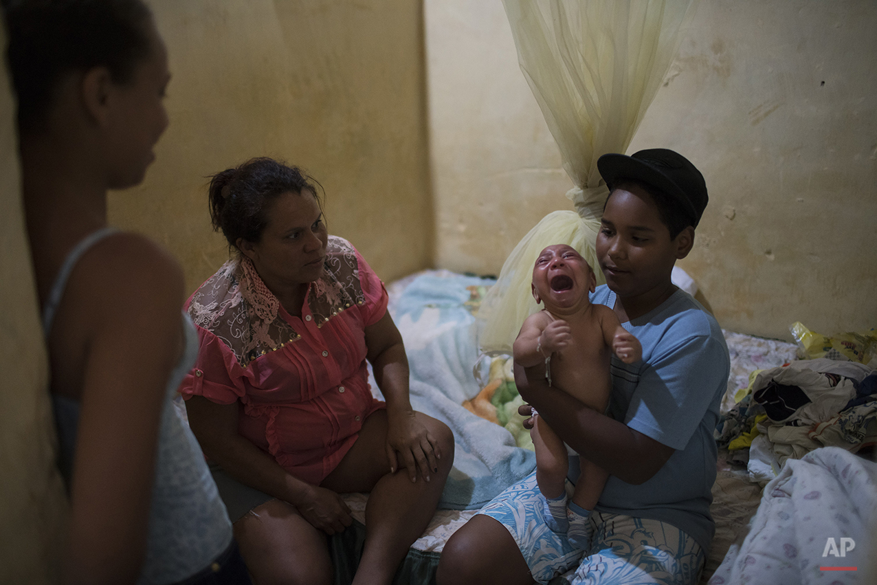 In this Jan. 30, 2016 photo, Solange Ferreira, left, watches as her nephew Jhonnata tries to calm Jose Wesley, in their house in Bonito, Pernambuco state, Brazil. According to Ferreira when his screaming gets bad nobody in the house can stand it. Only the water bucket will calm him down. (AP Photo/Felipe Dana)
