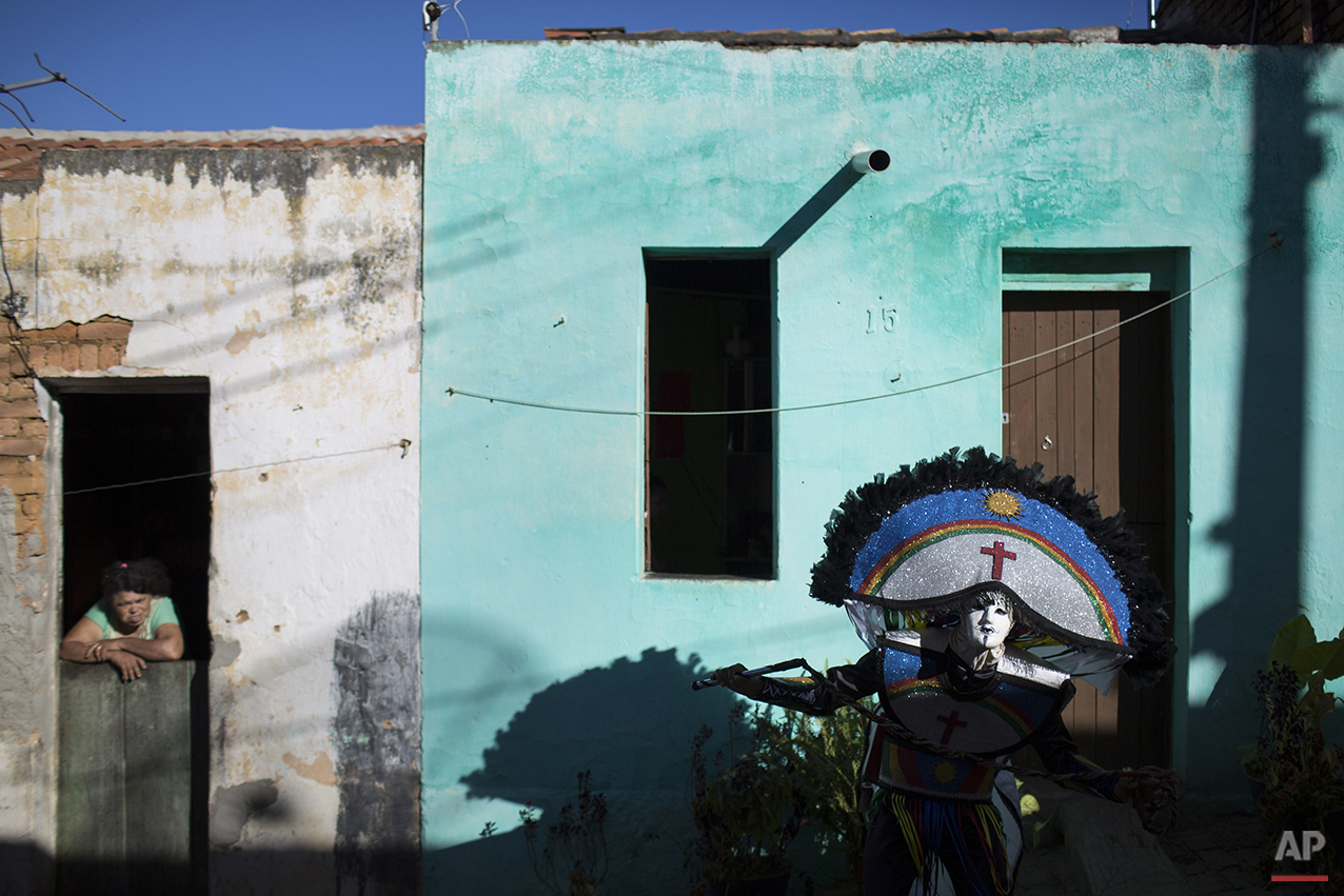"""A resident watches from her home a """"Careta"""" parading through the streets of Triunfo, Brazil, Monday, Feb. 8, 2016. The traditional festivity dates back almost a century. Residents say it was created in this small town by two men who weren't allowed to take part in a folk celebration because they were drunk. (AP Photo/Felipe Dana)"""