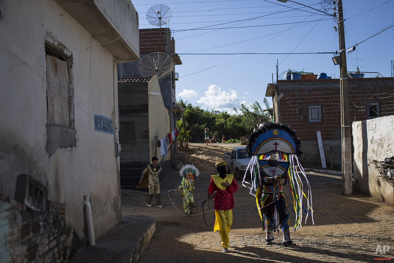 """A group of """"Caretas"""" walk together before parading at Carnival celebrations in Triunfo, Brazil, Monday, Feb. 8, 2016. Residents in this small town say the tradition began after two men were forbidden to take part in a folk celebration due to their drunken behavior. As retaliation, the pair roamed the streets wearing masks painted with sour expressions. (AP Photo/Felipe Dana)"""