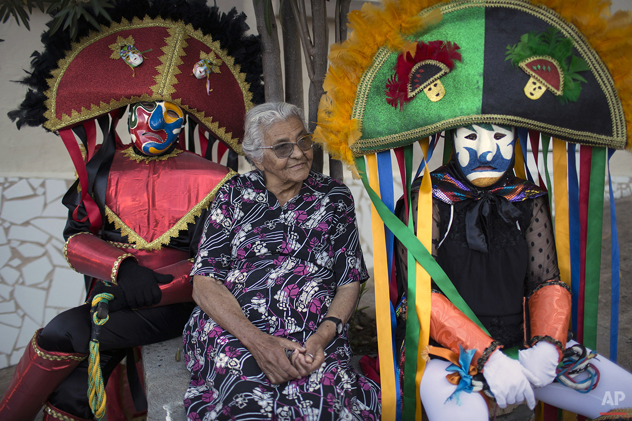 """""""Caretas"""" performers sit next to an elderly woman during Carnival celebrations in Triunfo, Brazil, Monday, Feb. 8, 2016. Revelers take to the streets in hand-made costumes that feature huge hats, long whips and scowling masks.  (AP Photo/Felipe Dana)"""