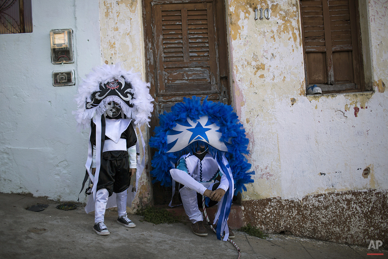 """Young """"Caretas"""" in costume wait for the start of their Carnival parade in Triunfo, Brazil, Monday, Feb. 8, 2016. """"Caretas"""" groups parade through town wearing their dour masks and cracking whips. (AP Photo/Felipe Dana)"""