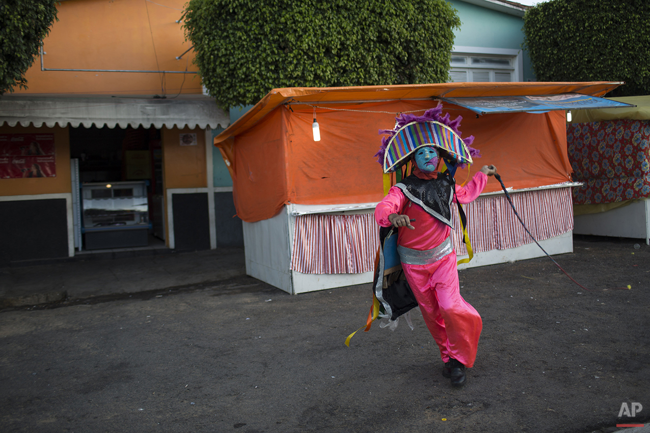 """A """"Careta"""" cracks his whip during Carnival celebrations in Triunfo, Brazil, Monday, Feb. 8, 2016. Residents in this small town say the Careta tradition began after two men were forbidden to take part in a folk celebration due to their drunken behavior. As retaliation, the pair roamed the streets wearing masks painted with sour expressions. Every Carnival since then, """"Caretas' groups parade through Triunfo wearing their dour masks and cracking whips. (AP Photo/Felipe Dana)"""