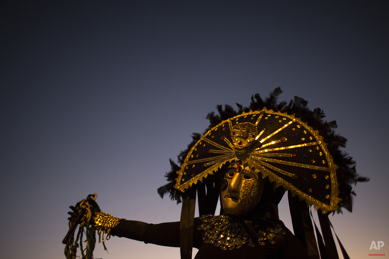 """A """"Careta"""" performs in the street during Carnival in Triunfo, Brazil, Monday, Feb. 8, 2016. Far from the glitz and glamour of Rio de Janeiro's famous Sambadrome parades, people in this northeast Brazilian town put a frown on their Carnival celebration. (AP Photo/Felipe Dana)"""