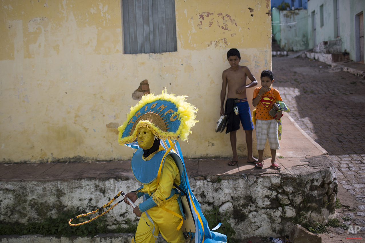"""A young """"Careta"""" makes his way to a parade during Carnival in Triunfo, Brazil, Monday, Feb. 8, 2016. Wearing frowning masks, Caretas Carnival revelers make their own costumes, featuring huge hats and long whips. (AP Photo/Felipe Dana)"""