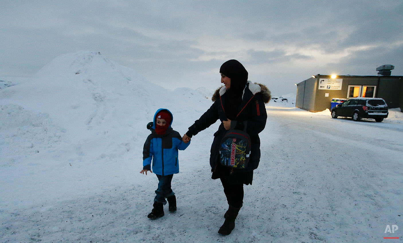 In this photo taken Thursday, Feb. 4, 2016 in Hammerfest, northern Norway, refugee Huda al Haggar and her son Omar from Sanaa in Yemen talk to the Associated Press at the northernmost refugee camp in the world. Waiting for their asylum claims to be processed, hundreds of people in emergency shelters in Hammerfest and neighboring towns are slowly getting used to the extreme climate and unfamiliar customs of the High North. They say they have adapted to the cold _ the temperature rarely drops below minus 10 degrees C (14 F) along the coast, though it gets much colder further inland. It's the darkness that throws them off. (AP Photo/Alastair Grant)