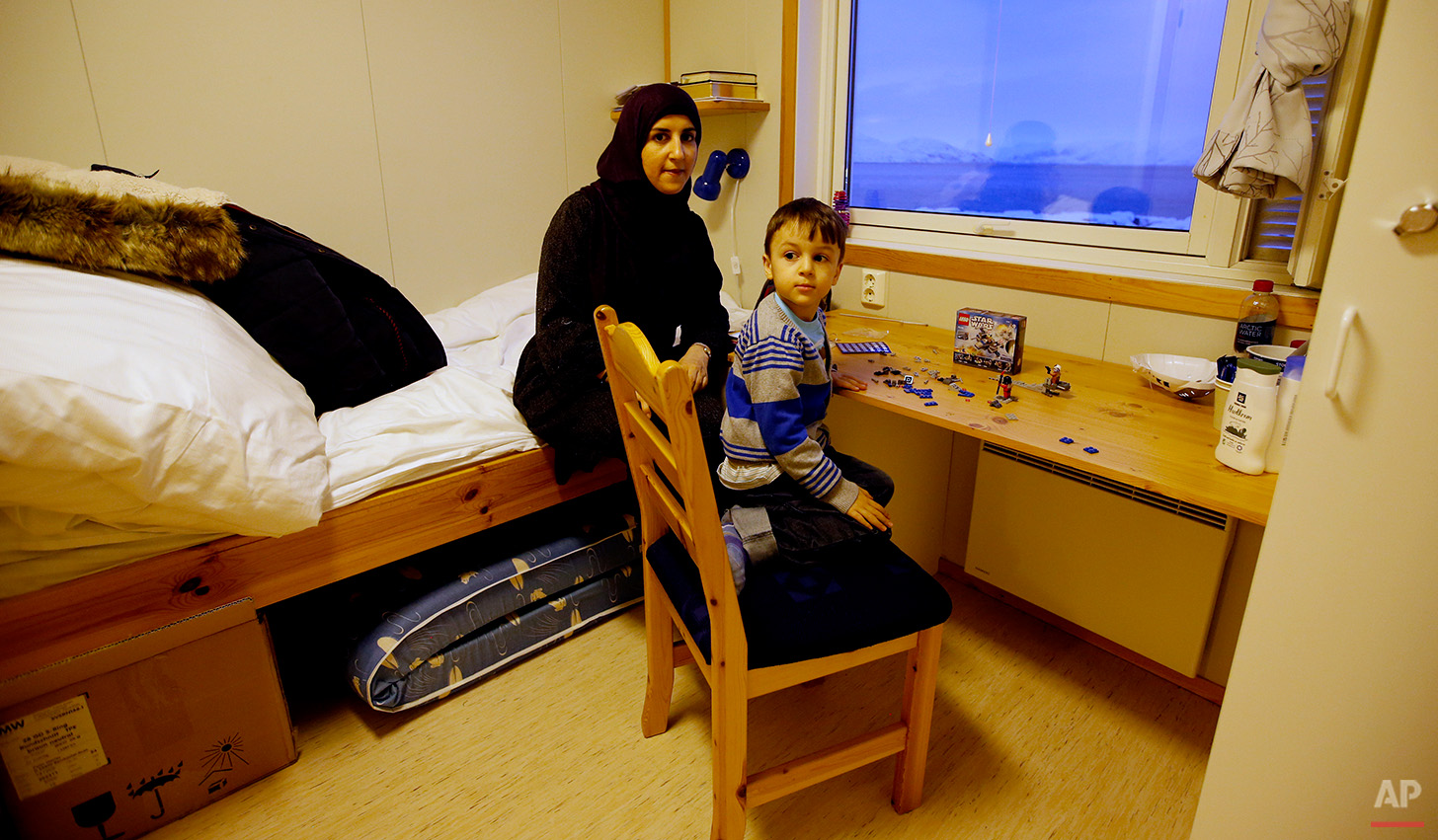 In this photo taken Thursday, Feb. 4, 2016 in Hammerfest, northern Norway, refugee Huda al Haggar and her son Omar from Sanaa in Yemen talk to the Associated Press at the northernmost refugee camp in the world. From her modest room, Huda al-Haggar admires the wonderland of snow and ice, a sight so different from her native Yemen, where a Saudi airstrike destroyed her home, forcing her to flee with her young son. (AP Photo/Alastair Grant)