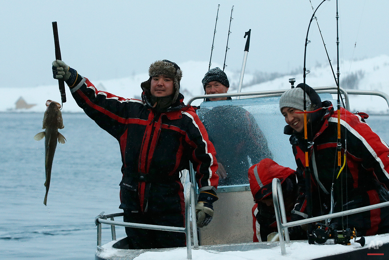 In this photo taken Tuesday, Feb. 2, 2016 Stig Erland Hansen, centre, owner of the Altnes camp, returns from a fishing trip with asylum seekers who show off their catch on the island of Seiland, northern Norway. Waiting for their asylum claims to be processed, hundreds of people in emergency shelters in Hammerfest and neighboring towns are slowly getting used to the extreme climate and unfamiliar customs of the High North. They say they have adapted to the cold _ the temperature rarely drops below minus 10 degrees C (14 F) along the coast, though it gets much colder further inland.  (AP Photo/Alastair Grant)