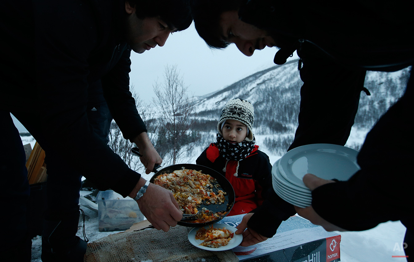 Afghan asylum seeker Roheek Yausofi waits his turn for food cooked on an open fire, with fish caught the day before by his father, on the island of Seiland, northern Norway, Tuesday, Feb. 2, 2016. Waiting for their asylum claims to be processed, hundreds of people in emergency shelters in Hammerfest and neighboring towns are slowly getting used to the extreme climate and unfamiliar customs of the High North. They say they have adapted to the cold _ the temperature rarely drops below minus 10 degrees C (14 F) along the coast, though it gets much colder further inland. (AP Photo/Alastair Grant)