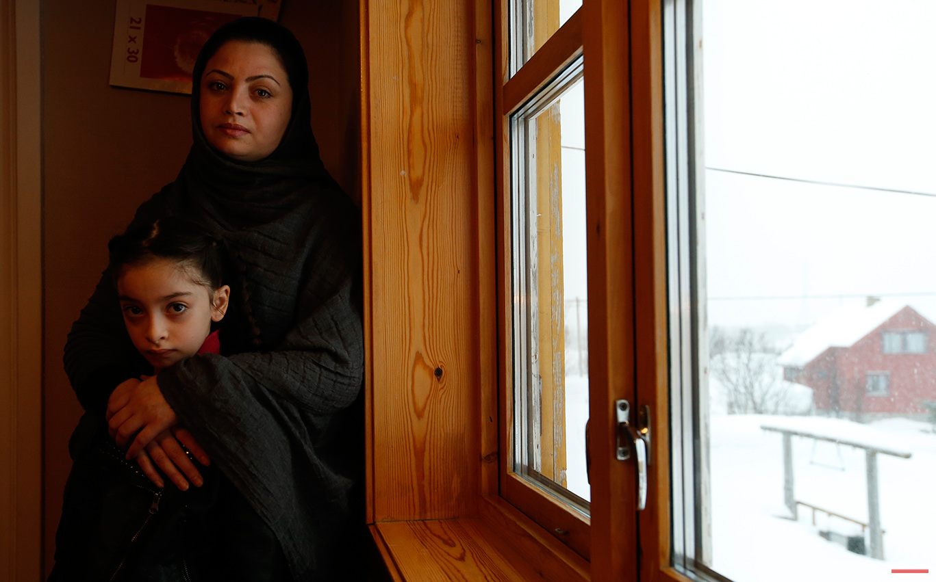 In this photo taken Tuesday, Feb. 2, 2016, Afghan asylum seekers Sufya Nawabi and her daughter Helanar pose for a photograph as they speak to the Associated Press in her temporary apartment at the Altnes camp on the island of Seiland, northern Norway. Waiting for their asylum claims to be processed, hundreds of people in emergency shelters in Hammerfest and neighboring towns are slowly getting used to the extreme climate and unfamiliar customs of the High North. (AP Photo/Alastair Grant)