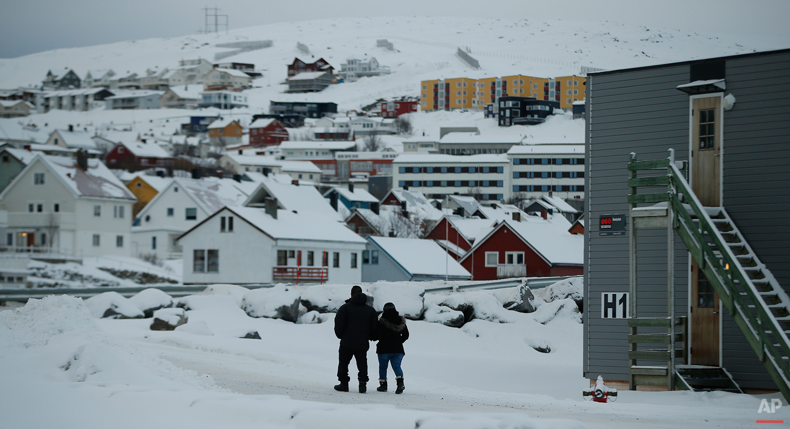 In this photo taken Thursday, Feb. 4, 2016, asylum seekers leave the refugee camp in Hammerfest to walk to the town's centre in northern Norway. Waiting for their asylum claims to be processed, hundreds of people in emergency shelters in Hammerfest and neighboring towns are slowly getting used to the extreme climate and unfamiliar customs of the High North. They say they have adapted to the cold _ the temperature rarely drops below minus 10 degrees C (14 F) along the coast, though it gets much colder further inland. It's the darkness that throws them off. (AP Photo/Alastair Grant)
