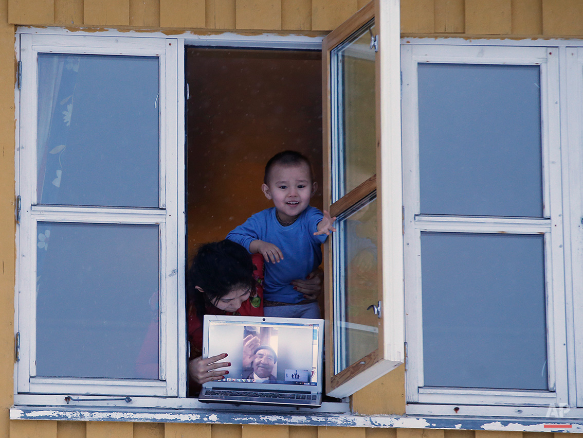 In this photo taken Tuesday, Feb. 2, 2016 Afghan asylum seekers hold a laptop which shows a picture of a grandparent, as men return from a fishing trip at their temporary accommodation at the Altnes camp on the island of Seiland, northern Norway. Waiting for their asylum claims to be processed, hundreds of people in emergency shelters in Hammerfest and neighboring towns are slowly getting used to the extreme climate and unfamiliar customs of the High North. (AP Photo/Alastair Grant)