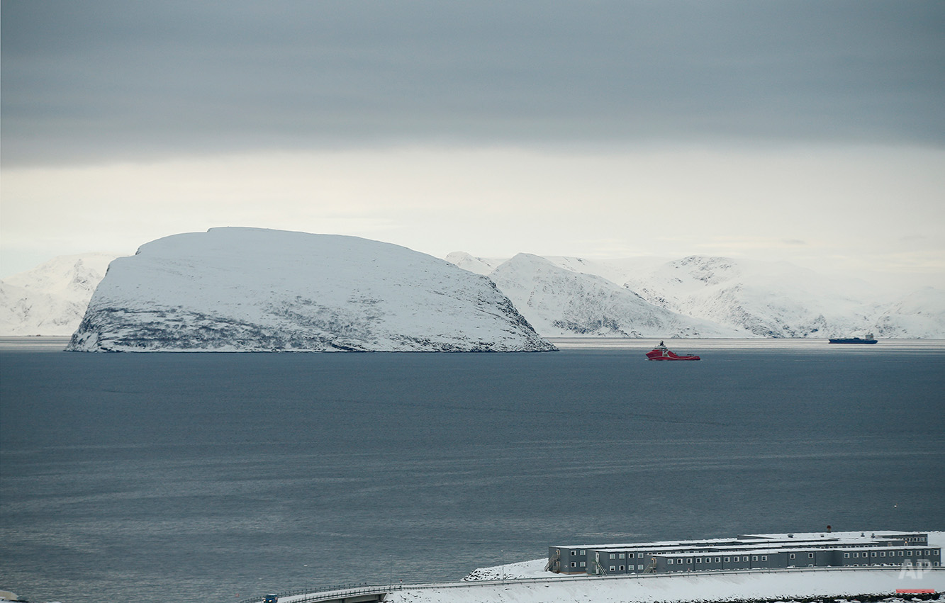 In this photo taken Thursday, Feb. 4, 2016, a view is shown towards the refugee camp in Hammerfest, northern Norway, and an inlet from the Barents Sea. After hiding below the horizon for two long months, the sun has finally risen in Hammerfest, casting a pale pink hue over the Arctic landscape surrounding the world's northernmost refugee shelter. (AP Photo/Alastair Grant)