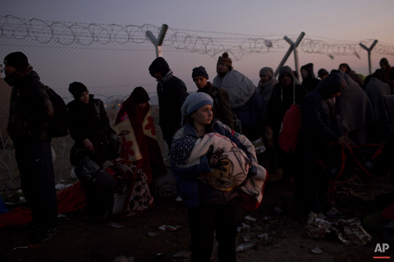 A woman holds her baby as she waits with other refugees in front of the wire fence that separates the Greek side from the Macedonian one, to be allowed to cross into Macedonia, at the northern Greek border station of Idomeni, Sunday, Dec. 6, 2015.