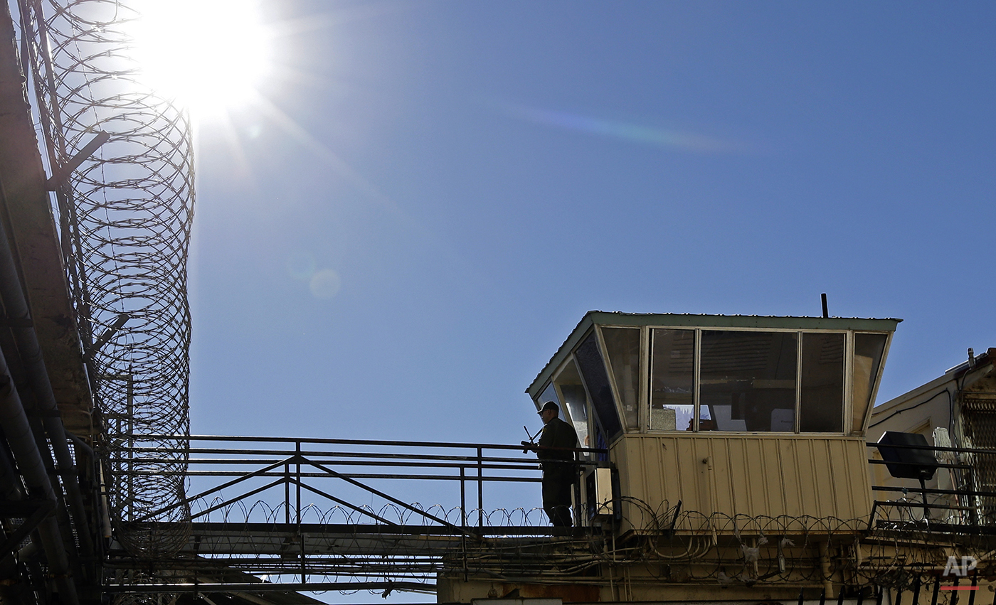 In this photo taken on Tuesday, Dec. 29, 2015, an armed guard stands watch on a gun ramp at San Quentin State Prison in San Quentin, Calif. With California's lethal injection protocol in limbo, the nearly 750 inmates at San Quentin State Prison, the nation's most populous death row, are more likely to die from natural causes or suicide than execution. The inmates await a final decision on a proposed one-drug execution method and the possibility that voters in 2016 will scrap the death penalty altogether. (AP Photo/Ben Margot)