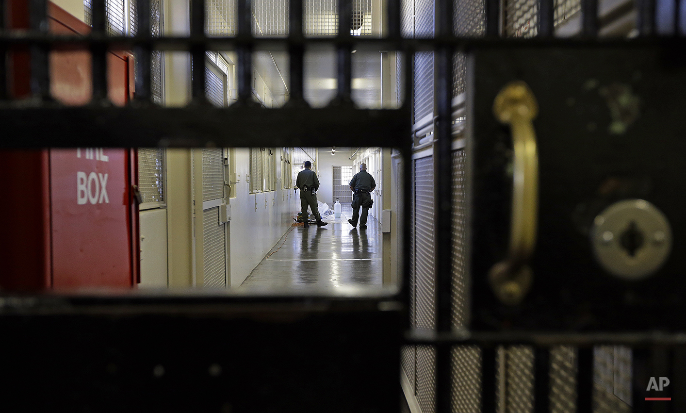 In this photo taken on Tuesday, Dec. 29, 2015, prison guards walk down a corridor in the Adjustment Center at San Quentin State Prison in San Quentin, Calif. With California's lethal injection protocol in limbo, the nearly 750 inmates at San Quentin State Prison, the nation's most populous death row, are more likely to die from natural causes or suicide than execution. (AP Photo/Ben Margot)