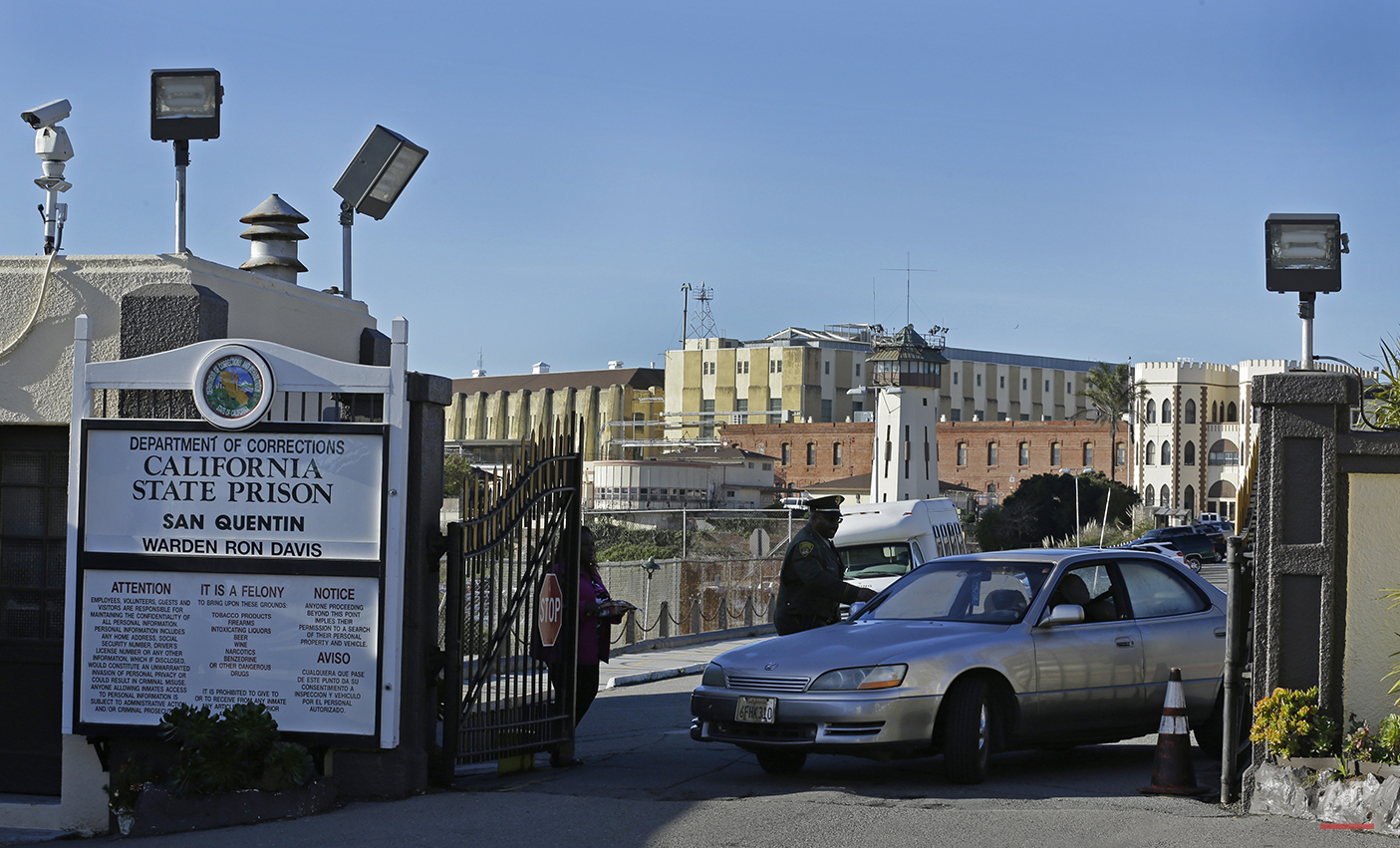In this photo taken on Tuesday, Dec. 29, 2015, a guard checks identification of a person leaving the east gate of San Quentin State Prison in a vehicle in San Quentin, Calif. With California's lethal injection protocol in limbo, the nearly 750 inmates at San Quentin State Prison, the nation's most populous death row, are more likely to die from natural causes or suicide than execution. The inmates await a final decision on a proposed one-drug execution method and the possibility that voters in 2016 will scrap the death penalty altogether. (AP Photo/Ben Margot)