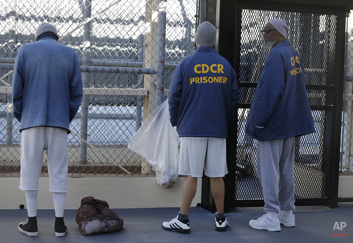 In this photo taken on Tuesday, Dec. 29, 2015, condemned inmates Scott Peterson, center, convicted of murdering his wife Laci Peterson; and Larry Hazlette, right, speak on the recreation yard at San Quentin State Prison in San Quentin, Calif. With California's lethal injection protocol in limbo, the nearly 750 inmates at San Quentin State Prison, the nation's most populous death row, are more likely to die from natural causes or suicide than execution. The inmates await a final decision on a proposed one-drug execution method and the possibility that voters in 2016 will scrap the death penalty altogether. (AP Photo/Ben Margot)