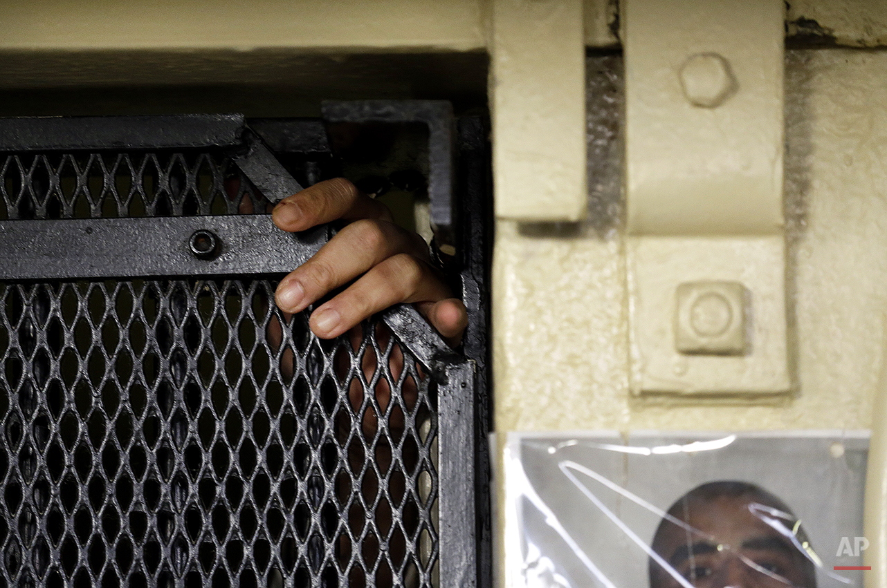 In this photo taken on Tuesday, Dec. 29, 2015, the fingers of Martin Navarette reach out of his cell on death row at San Quentin State Prison in San Quentin, Calif. With California's lethal injection protocol in limbo, the nearly 750 inmates at San Quentin State Prison, the nation's most populous death row, are more likely to die from natural causes or suicide than execution. The inmates await a final decision on a proposed one-drug execution method and the possibility that voters in 2016 will scrap the death penalty altogether. (AP Photo/Ben Margot)