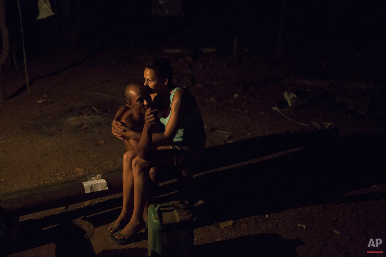 In this Nov. 15, 2015 photo, Amadeu de Jesus, 39, left, and Gleice da Conceicao, 29, sit together after dinner in Areinha, Minas Gerais state, Brazil. Amadeu began diamond mining when he was only 14-years-old. He met Gleice in Areinha, where she works as a cook and searches for diamonds in her free time. (AP Photo/Felipe Dana)