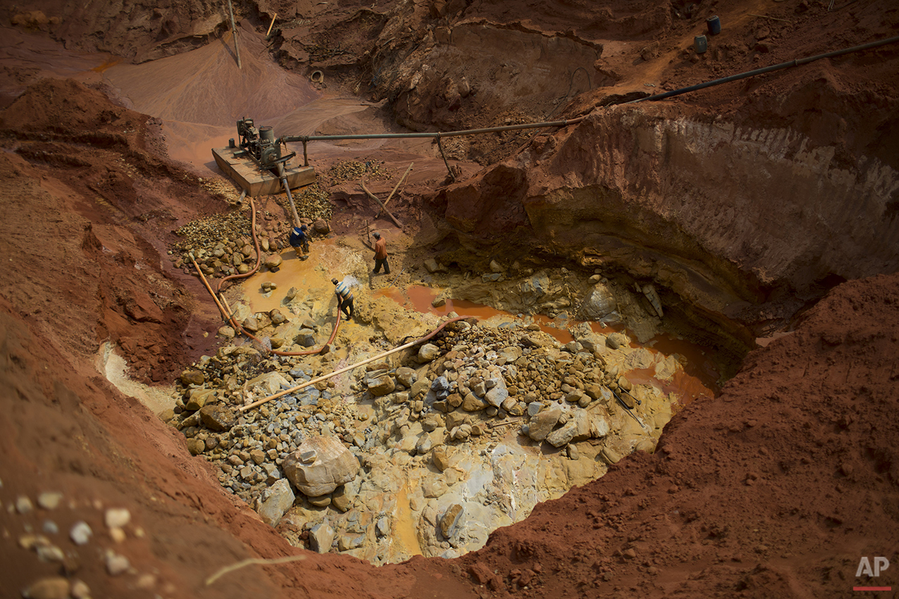 In this Nov. 14, 2015 photo, artisanal diamond miners use a water pump to separate rocks at an abandoned mine in Areinha, Minas Gerais state, Brazil. The devastated area known as Areinha is a no man's land where small groups of rural miners try their luck in the craters left behind by multinational mining companies. (AP Photo/Felipe Dana)