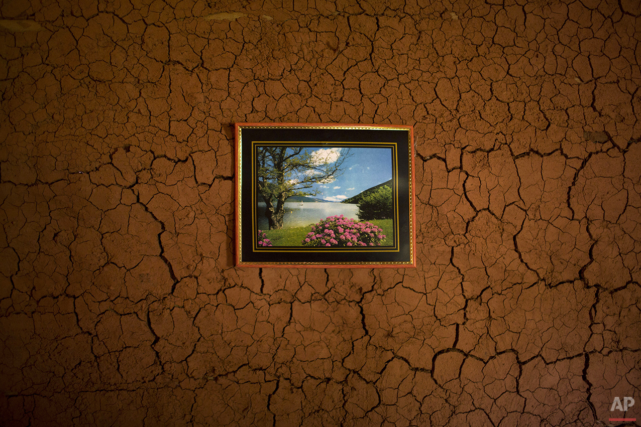 In this Nov. 13, 2015 photo, a picture hangs on the wall inside an artisanal diamond miner's home in Areinha, Minas Gerais state, Brazil. The devastated area abandoned by giant mining corporations is now a no man's land where small groups of rural workers try their luck with manual techniques and little to no infrastructure. (AP Photo/Felipe Dana)