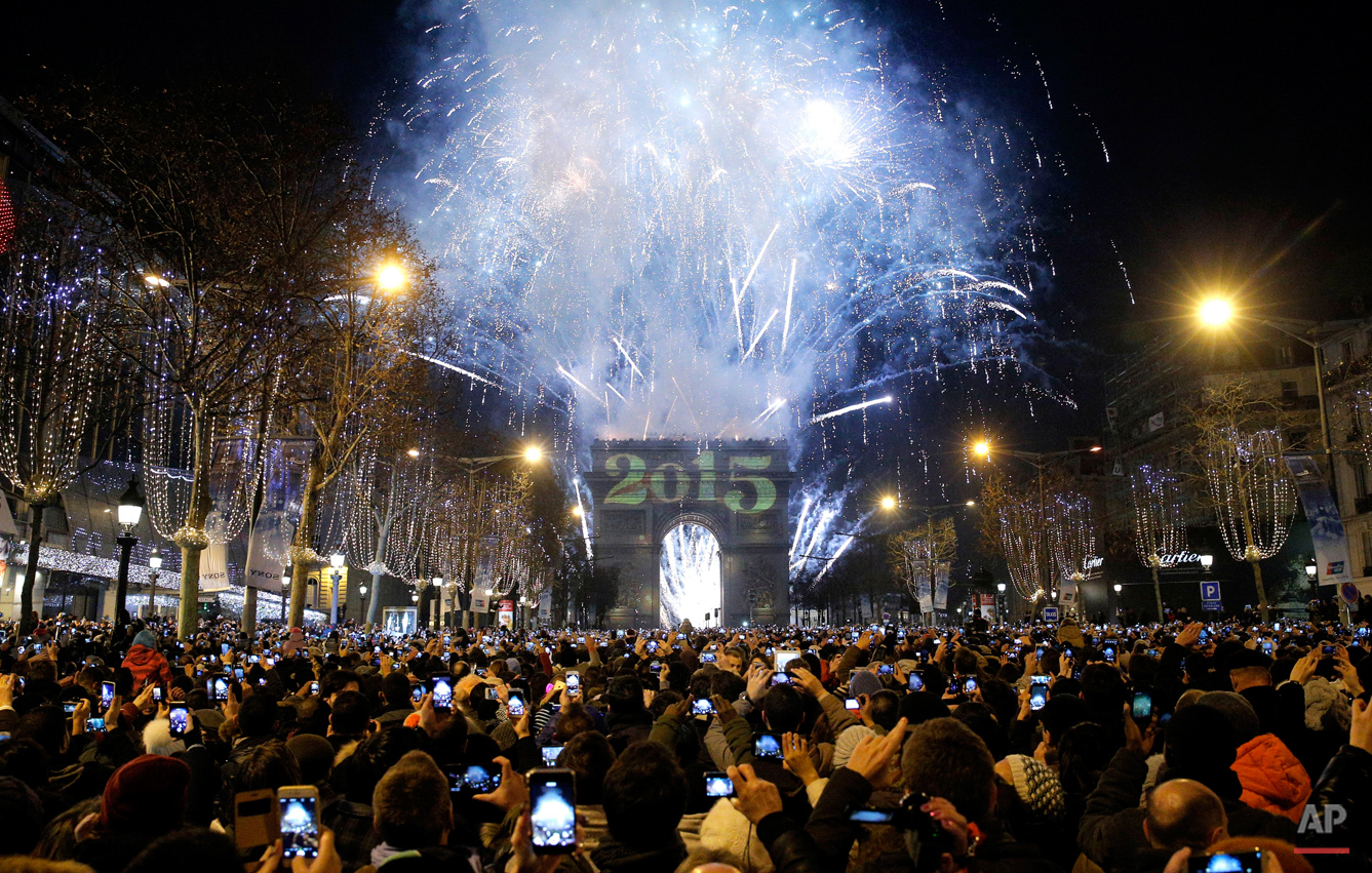 Revellers photograph fireworks over the Arc de Triomphe as they  celebrate the New Year on the Champs Elysees avenue in Paris, France, Thursday, Jan. 1, 2015. (AP Photo/Christophe Ena)
