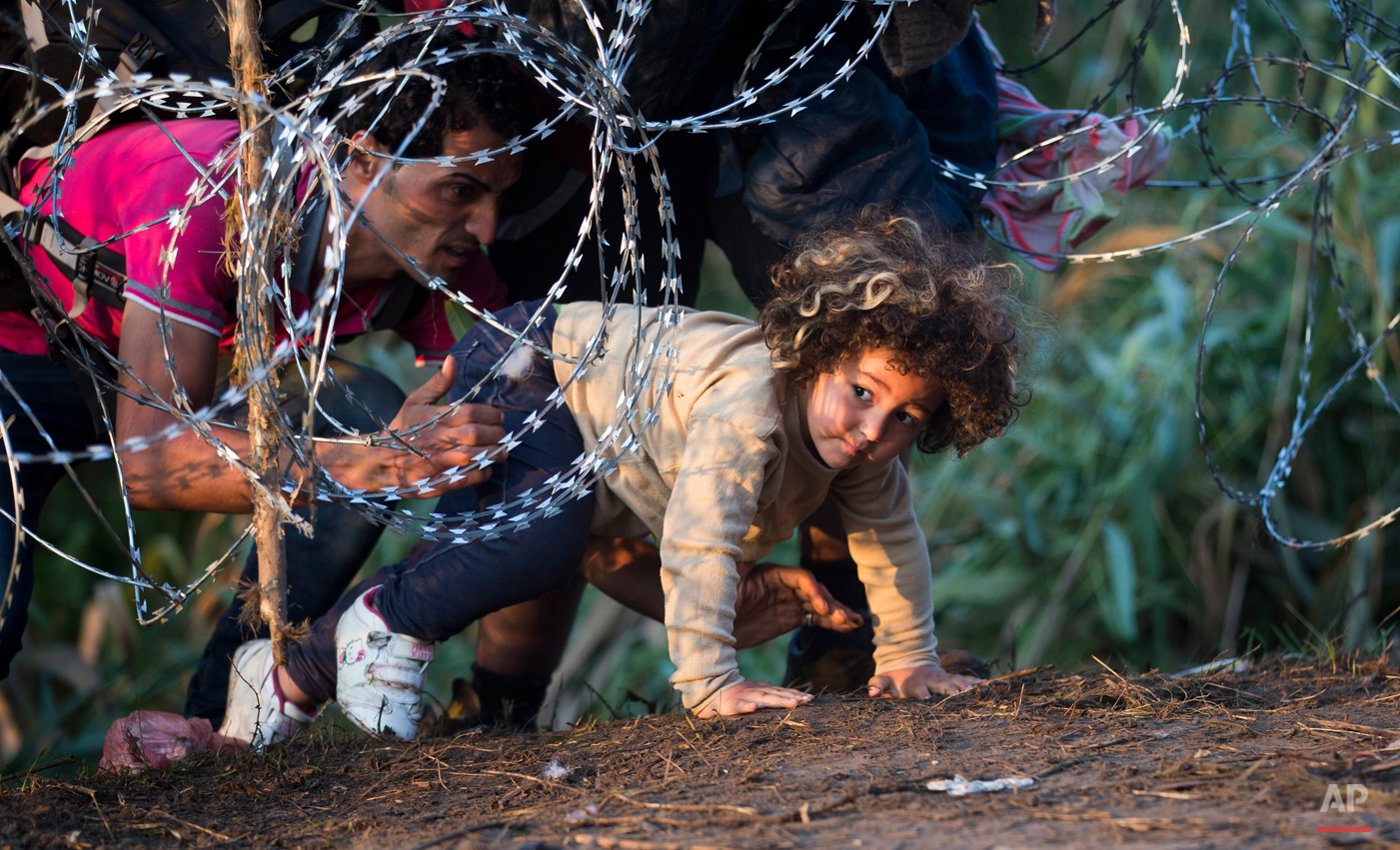 In this Thursday, Aug. 27, 2015 photo, a child is helped cross from Serbia to Hungary through the barbed wire fence near Roszke, southern Hungary. Round the clock, thousands of refugees cross daily along the approximately 110-mile (175-kilometer) border with non-EU member Serbia to the south. (AP Photo/Darko Bandic)