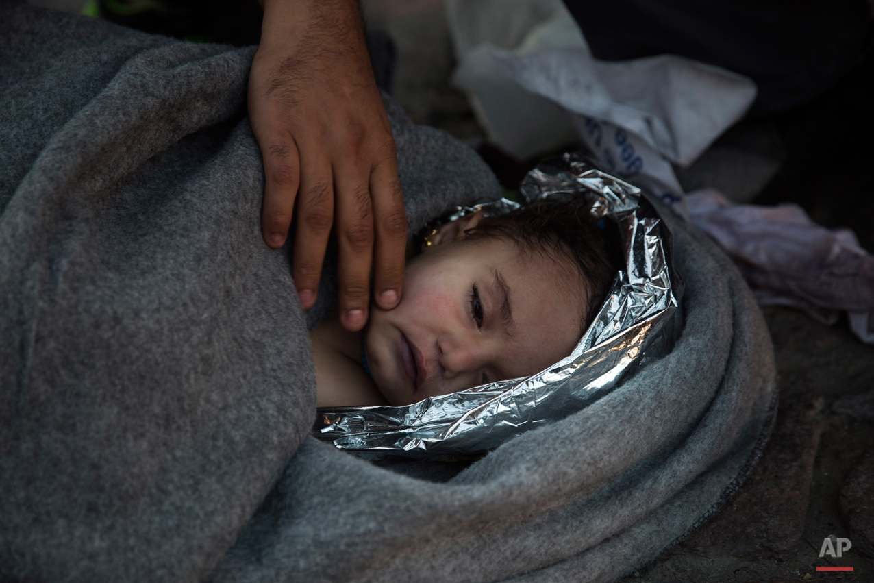 Paramedics and doctors care for a baby girl after a boat with refugees and migrants sunk while was crossing the Aegean sea from Turkey to the Greek island of Lesbos on Wednesday, Oct. 28, 2015. (AP Photo/Santi Palacios)