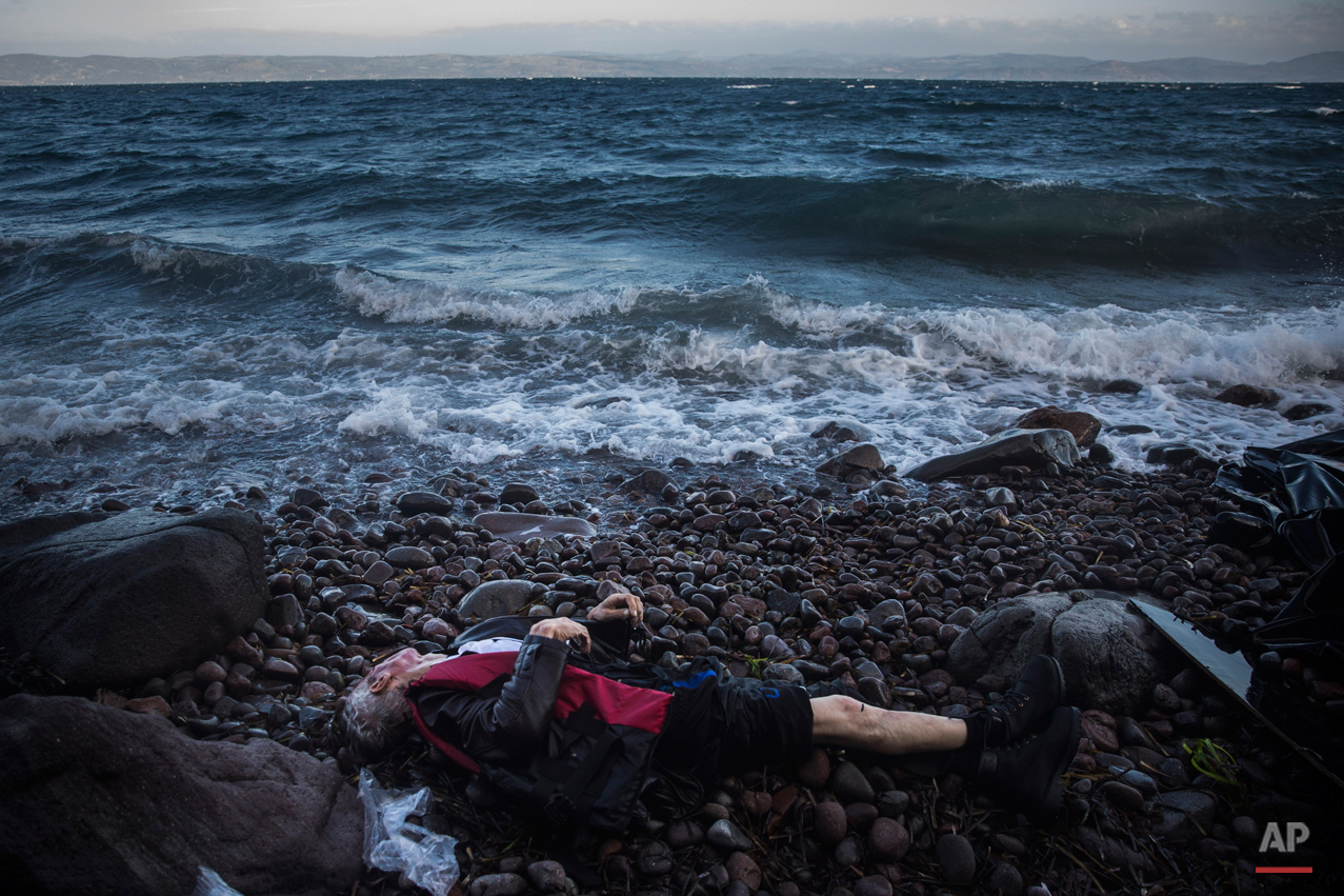 The lifeless body of an elderly unidentified man is seen on the beach after washing up on the shoreline at the village of Skala, on the Greek island of Lesbos, on Sunday, Nov. 1, 2015. Authorities recovered more bodies on Lesbos and the Greek island of Samos Sunday as thousands continue to cross from the nearby coast of Turkey despite worsening weather. Greece is pressing the European Union for additional support for their massive daily search and rescue operations. (AP Photo/Santi Palacios)