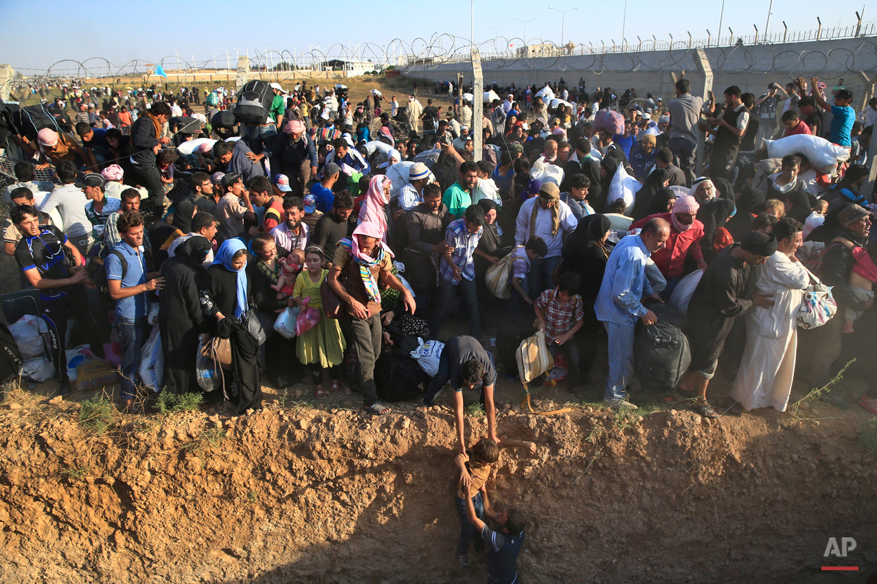 Syrian refugees walk into Turkey after breaking the border fence and crossing from Syria in Akcakale, Sanliurfa province, southeastern Turkey, Sunday, June 14, 2015. The mass displacement of Syrians across the border into Turkey comes as Kurdish fighters and Islamic extremists clashed in nearby city of Tal Abyad. (AP Photo/Lefteris Pitarakis)